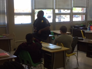 Officer talks with students